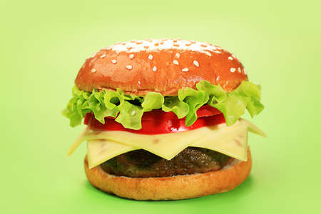 Appetizing cheeseburger over green background. photo
