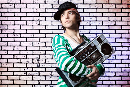 Trendy young man posing  against a brick wall with tape recorder.  photo