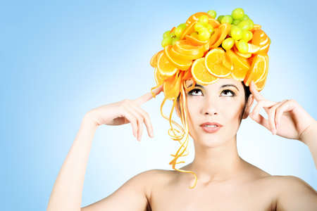Shot of a beautiful young woman with fruits headwear. Food concept, healthcare. photo