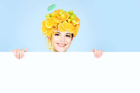 Shot of a beautiful young woman with fruits headwear holding white board. Food concept, healthcare. photo