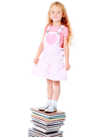 Portrait of a little girl standing on a stack of books. Isolated over white background. photo