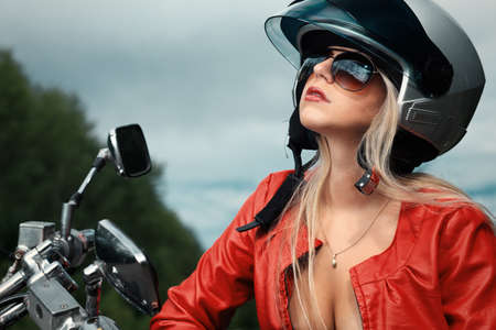 Shot of an attractive woman biker posing near her motorcycle. photo
