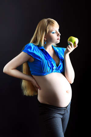 Portrait of a beautiful pregnant woman eating fresh apple. Over black background. photo