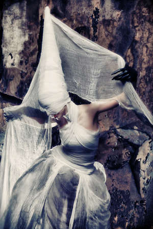 Shot of a twilight girl in white dress. Halloween, horror. photo