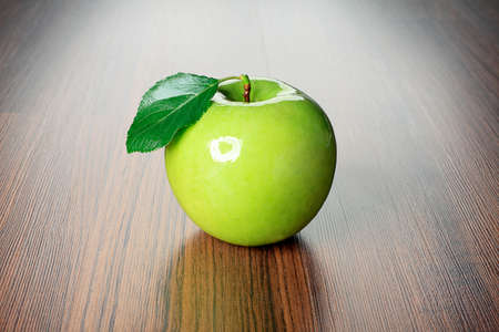 Shot of a fresh green apple with green leaf on a table. Stock Photo - 7498955