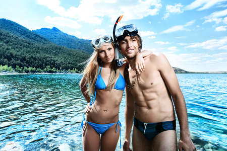 Happy young couple with snorkelling gear standing on a sea beach. Stock Photo