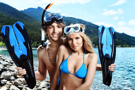 sky diving: Happy young couple with snorkelling gear standing on a sea beach. Stock Photo