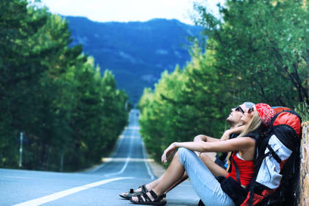 バックパック: かなり若い女性観光客の道路に沿ってヒッチハイクします。