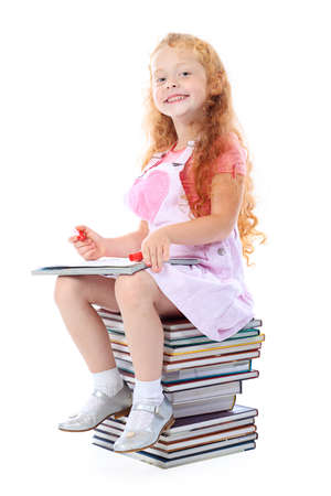 homestudy: Portrait of a little girl sitting on a stack of books. Isolated over white background.