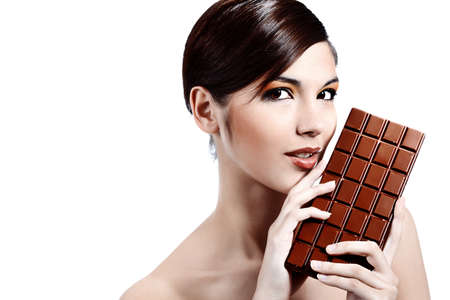 Shot of a beautiful young woman holding big chocolate bar. Stock Photo - 7552230
