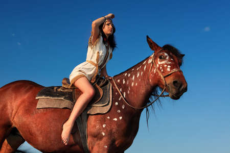 rodeo cowgirl: Beautiful young woman posing with a brown horse.