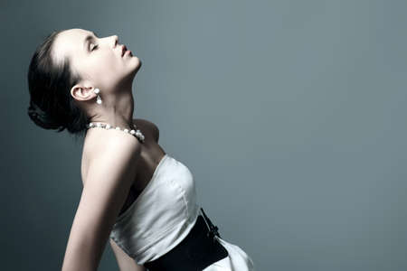 Fashion photo, a model is  posing over grey background photo
