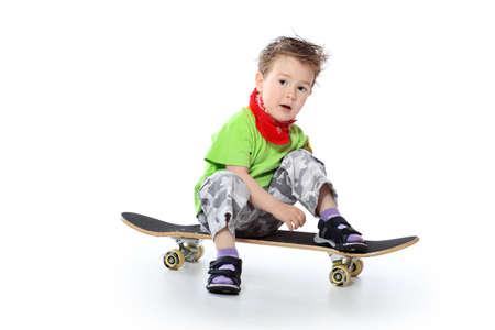 kinder: Colpo di un ragazzino alla moda di posa con skateboard. Isolato su sfondo bianco.