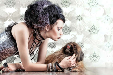 Portrait of a fashionable lady with a dog over vintage background. photo