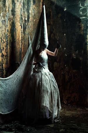 Shot of a twilight girl in white dress. Halloween, horror. photo
