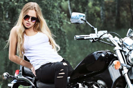 Shot of an attractive woman biker posing on her motorcycle. Stock Photo - 7632771