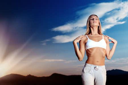 respiracion: Esbelta joven haciendo ejercicios de yoga al aire libre.