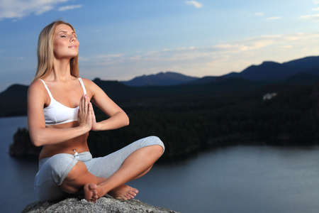 Slender young woman doing yoga exercise outdoors. photo