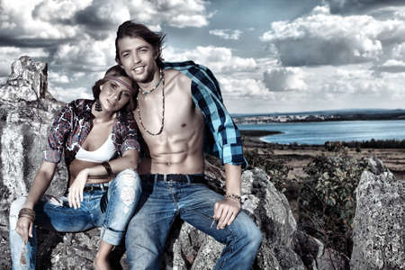 man in jeans: Beautiful young couple hippie posing together over picturesque landscape.