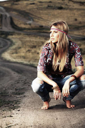 Beautiful young woman hippie posing over picturesque landscape. Stock Photo