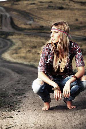 Mooie jonge vrouw hippie poseren over pittoreske landschap.