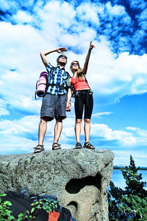 Couple of tourists are standing at the top of a mountain with a feeling of freedom. Stock Photo - 7647616