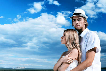 Beautiful young couple posing together over blue sky. photo