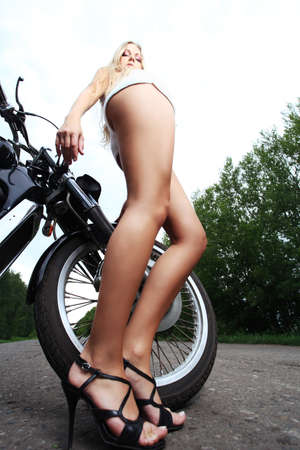 Shot of an attractive woman biker posing on her motorcycle. Stock Photo - 7647776