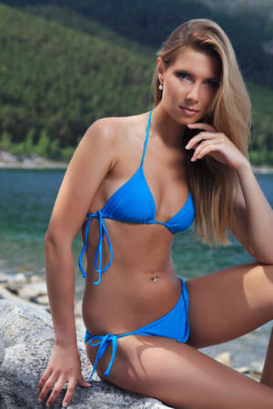 Beautiful young woman in bikini posing on a sea beach. photo
