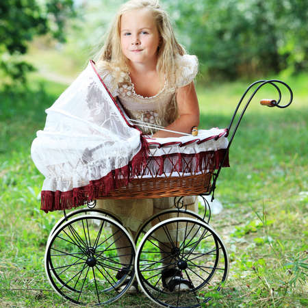 Shot of a cute girl walking with baby buggy at summer park. photo