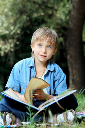 Shot of a little boy having a rest outdoor. photo