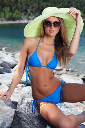 blonde bikini: Beautiful young woman in bikini posing on a sea beach.
