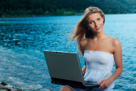 Happy young woman sitting  near the sea with a laptop. photo
