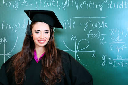 achiever: Educational theme: graduating student in academic gown in a classroom.