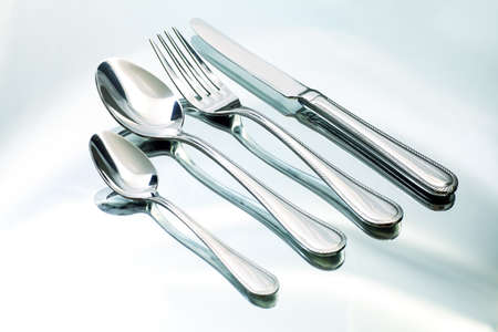 Silver fork, knife and spoons on a white plate. photo
