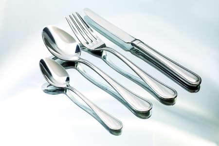 cuchara: Tenedor de plata, cuchillo y cucharas en un plato blanco.