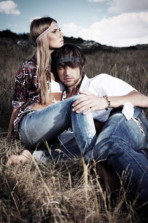 Beautiful young couple hippie posing together over picturesque landscape. photo