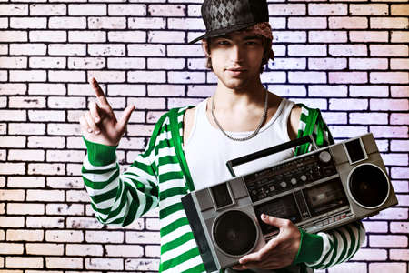 cool boy: Trendy young man posing  against a brick wall with tape recorder.