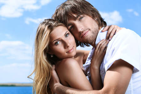 flirt: Beautiful young couple posing together over blue sky.