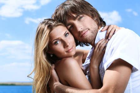 coquetear: Hermosa joven pareja posando juntos en el cielo azul.