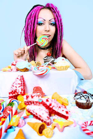 Portrait of a trendy girl with great number of sweets. photo