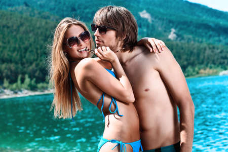 sunglasses beach: Happy young couple having a rest on a beach. Stock Photo