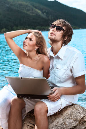 Happy young couple sitting together near the sea with a laptop. photo