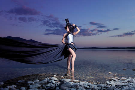 Fashion shot of the elegant young woman posing over beautiful landscape. photo