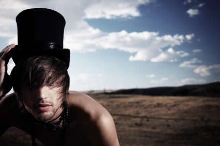 hat nude: Fashion shot of a handsome young man posing topless in top hat and bow tie over beautiful landscape. Stock Photo