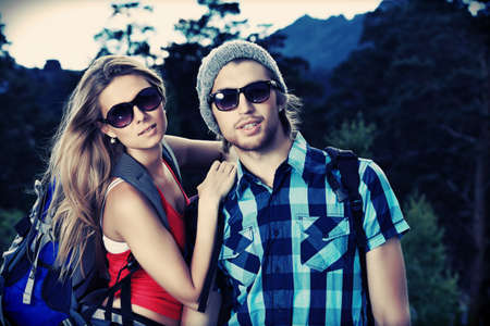 backpackers: Couple of tourists making their journey at the mountains. Stock Photo