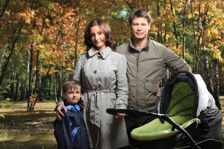 Happy family with two children walking at the autumn park. photo
