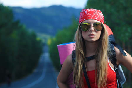 Pretty young woman tourist hitchhiking along a road. photo