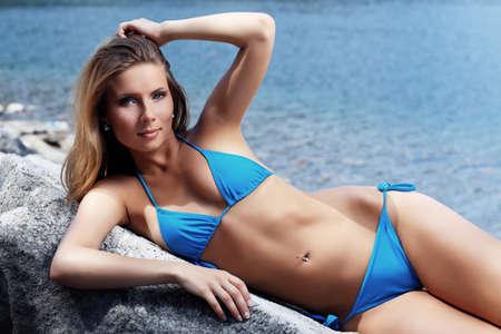 ni�as en bikini: Joven y bella mujer en bikini posando en una playa de mar.