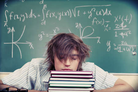 Educational theme: tired student in a classroom. Stock Photo - 7907146